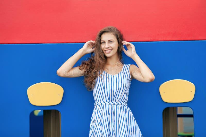 光的年轻深色的妇女镶边了白色蓝色礼服获得乐趣在室外的操场 免版税库存图片