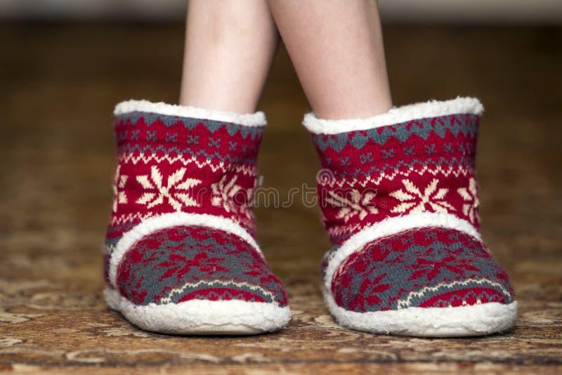 光秃的儿童腿和脚在红色冬天圣诞节起动与orna 免版税库存图片
