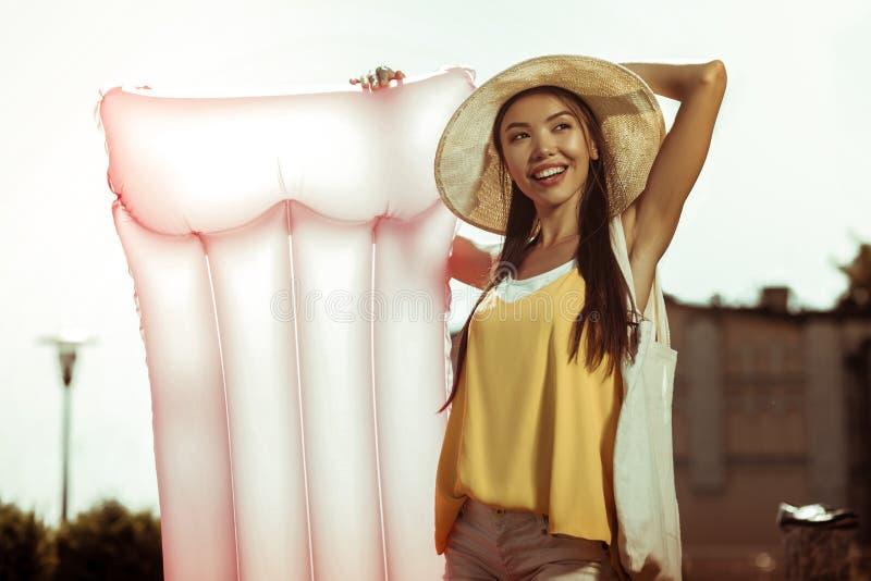 光芒四射的拿着一个桃红色可膨胀的气垫的妇女佩带的帽子 免版税库存照片