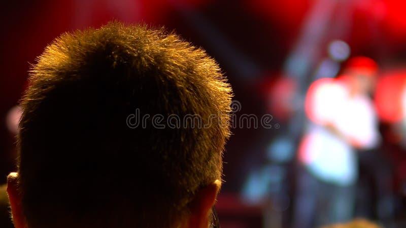 光音乐会的人现出轮廓的用rised的手  免版税图库摄影