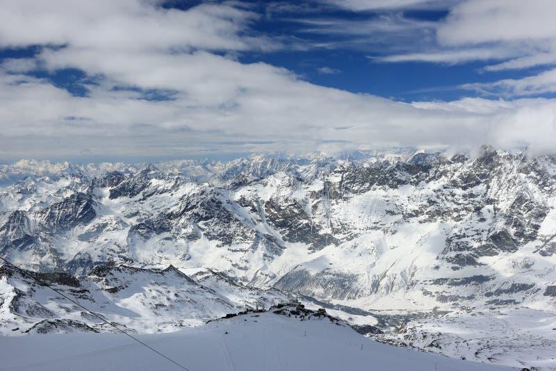 从克伦马塔角的看法3,883 m陈列瑞士阿尔卑斯的高山 瓦雷兹, Switzerland.Factories在瓦雷兹,瑞士散开抽烟作为工业废料到航空 库存照片