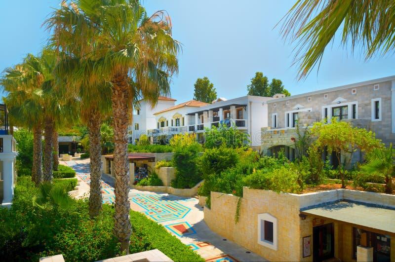 克利特海岛,希腊, 2011年7月01日:在旅馆热带别墅的看法游人客人的 绿色热带棕榈树 经典豪华 库存图片