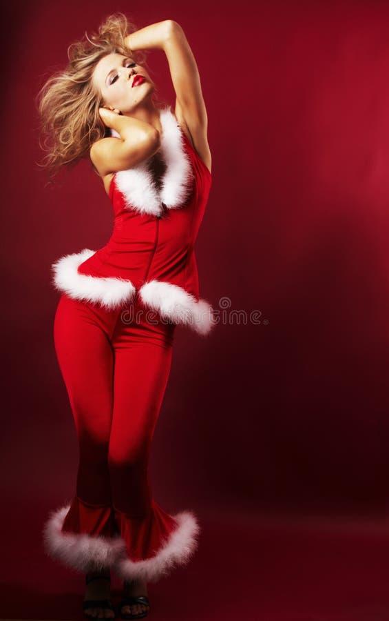 克劳斯给女孩圣诞老人性感佩带穿衣 免版税库存图片