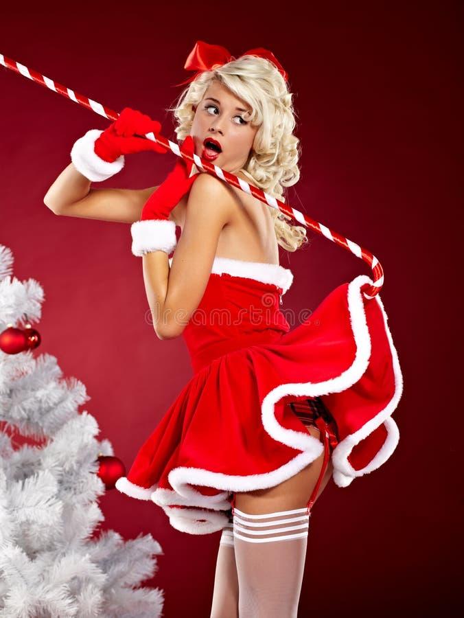 克劳斯给女孩针佩带的圣诞老人穿衣  库存图片