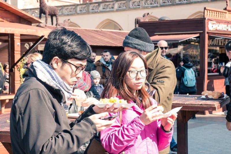 克拉科夫、波兰、2018年4月2日,年轻亚裔人和女孩吃s 图库摄影