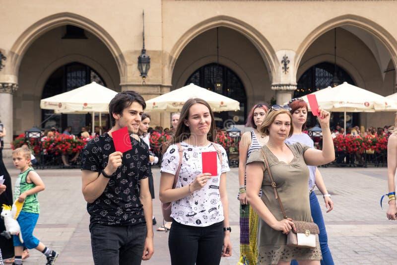 克拉科夫,波兰, 2018年6月01日,有红牌的三个人在Th 免版税库存图片