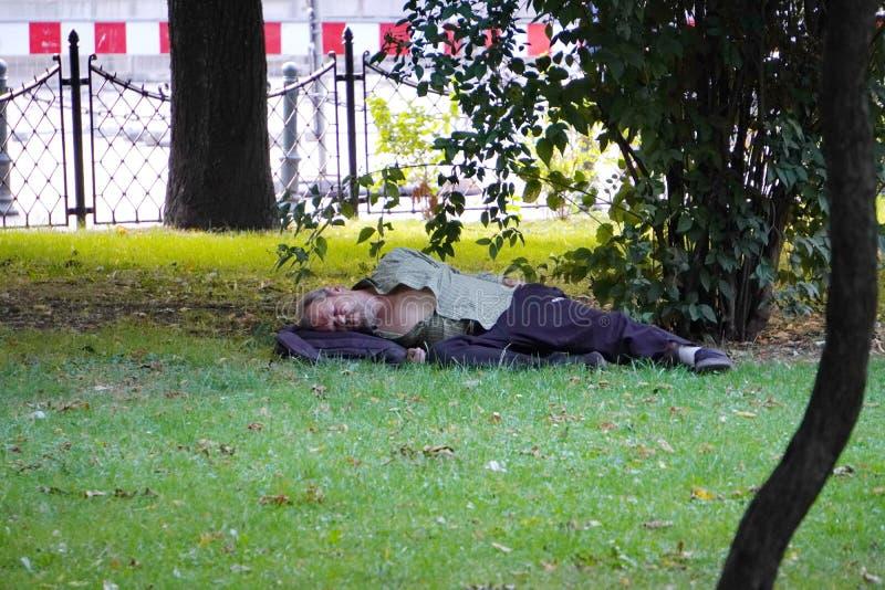 克拉科夫,波兰- 07 27 2019年:一个肮脏的无家可归的人在草坪睡觉在一棵树下在公园 二赖子在大城市的中心 免版税库存图片