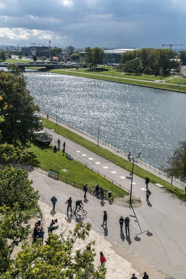 克拉科夫,波兰- 2018年9月23日:维斯瓦河的风景看法在白天,与树,草,进来的人们 免版税库存照片