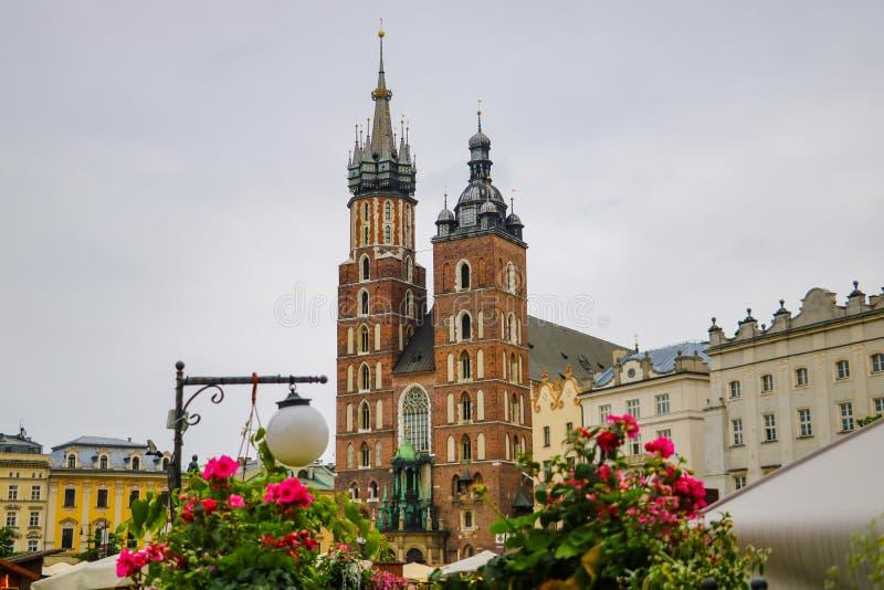 克拉科夫,波兰- 2019年5月21日:花看法在前景的,在背景中教会是在焦点外面 免版税库存图片