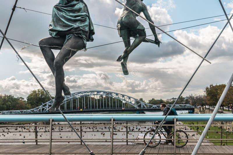 克拉科夫,波兰- 2018年9月23日:过Kladka Ojca Bernatka桥梁的骑自行车者在波兰,克拉科夫,有大的 库存照片