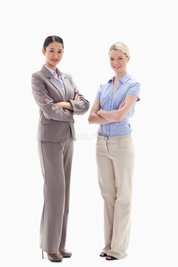 克服他们的胳膊的二名微笑的妇女 免版税库存照片