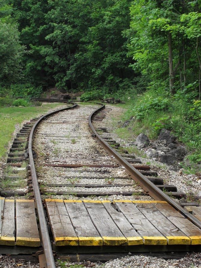 克服在木的铁轨 免版税库存照片