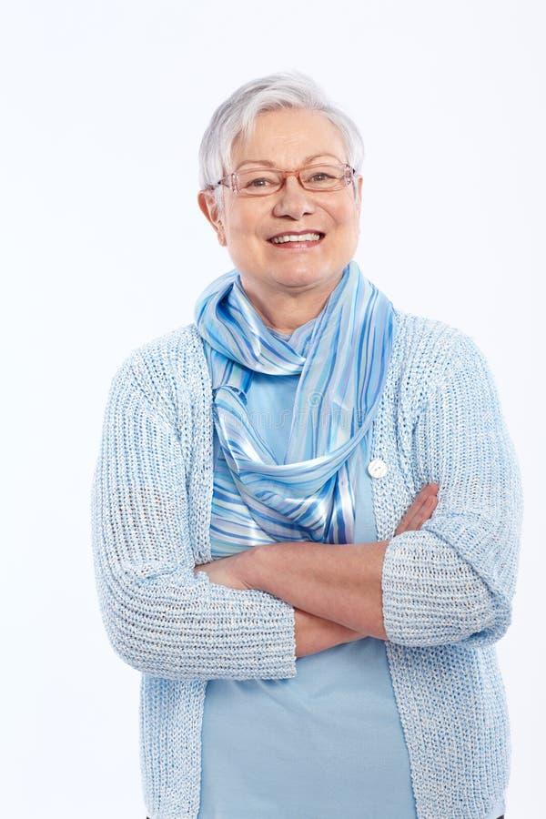 克服的微笑的年长夫人常设胳膊 免版税库存照片