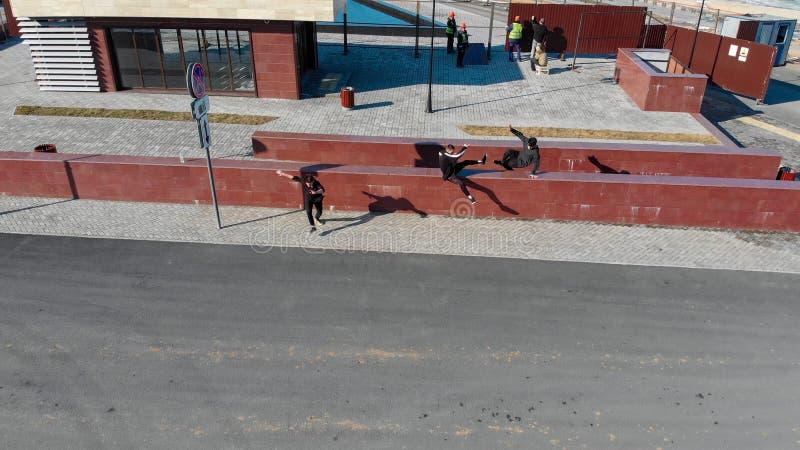 克服障碍和赛跑在路的三运动年轻人 r 免版税库存照片