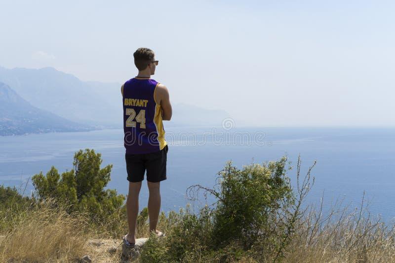 克罗地亚、2017年8月3日,年轻看海洋的人站立简而言之的, T恤杉和太阳镜 库存照片