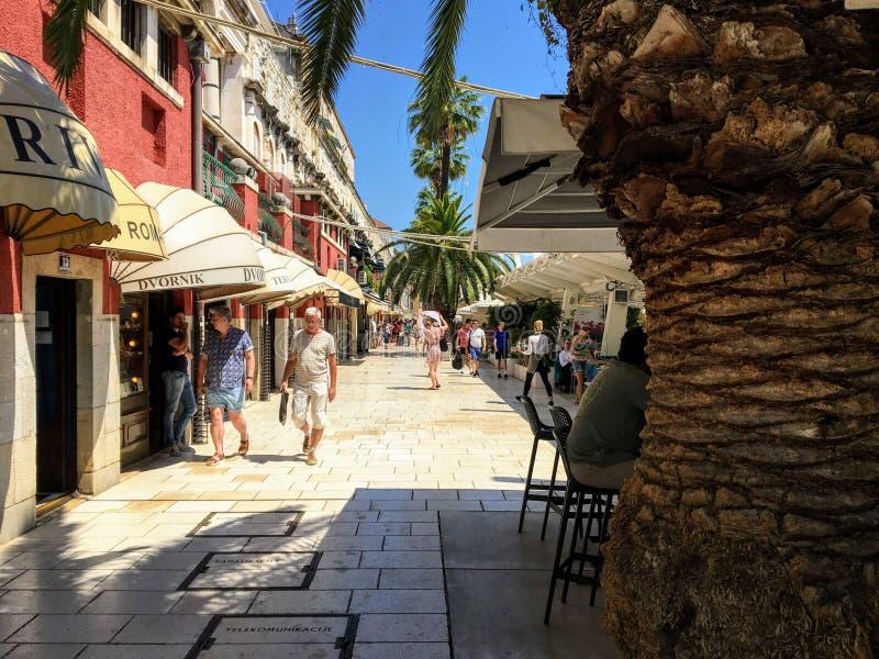 克罗地亚斯普利特海滨木板路上炎热的夏季 人们在众多商店和餐馆中漫步 库存照片