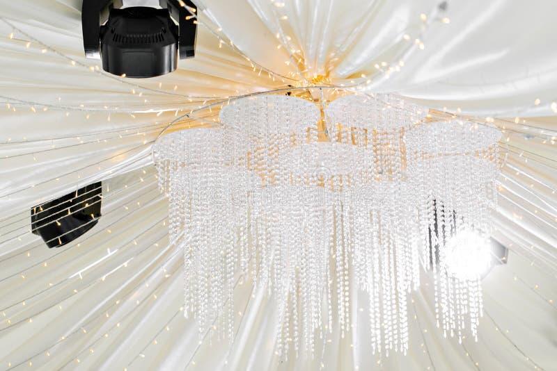 克里斯特尔枝形吊灯特写镜头 在一个帐篷下的美丽的宴会大厅结婚宴会的 婚礼帐篷的内部 库存图片