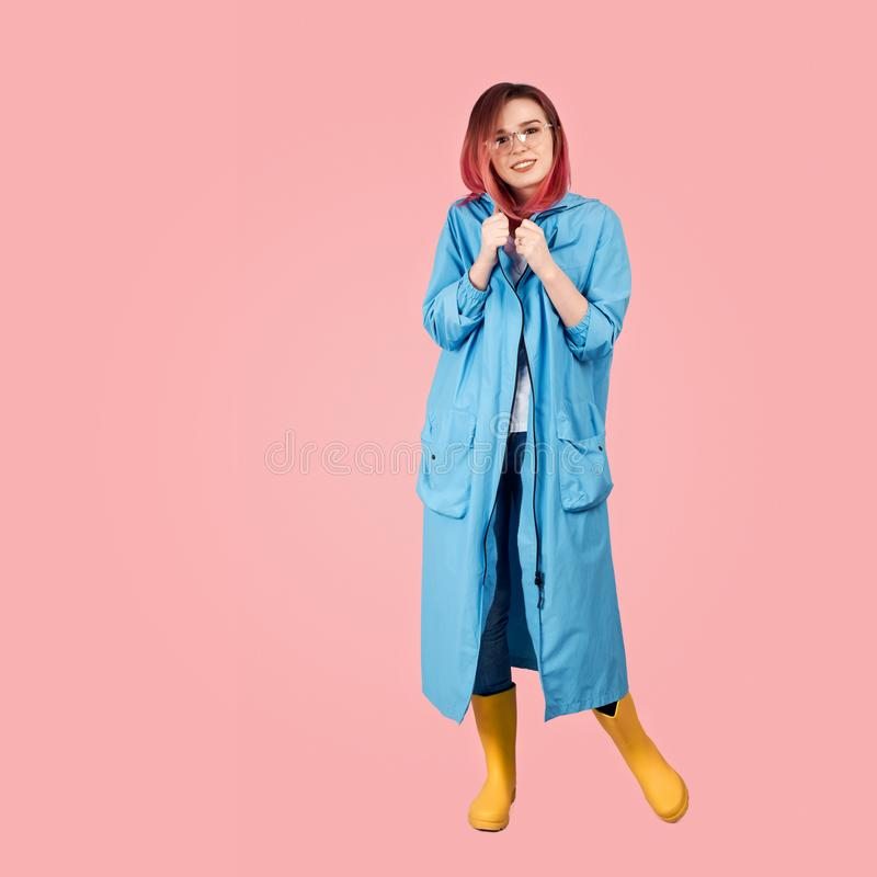 免受雨和高黄色胶靴保护的微笑的少女佩带的春天雨衣 免版税库存照片
