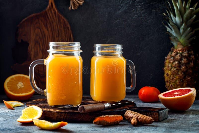 免疫促进,反激动的圆滑的人用桔子,菠萝,姜黄 戒毒所早晨汁液饮料 免版税库存照片