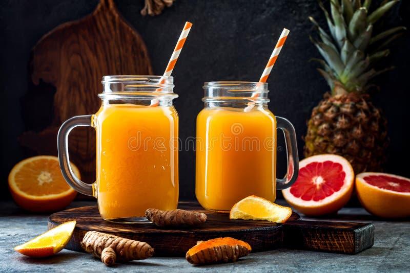 免疫促进,反激动的圆滑的人用桔子,菠萝,姜黄 戒毒所早晨汁液饮料 库存照片