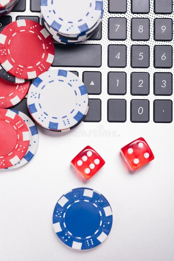 兑现芯片和立方体,折叠在膝上型计算机,打在互联网上的扑克 免版税库存照片