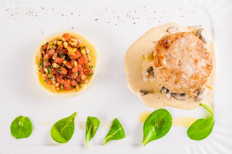 兔子炸肉排用土豆泥和蘑菇酱油在白色板材 图库摄影