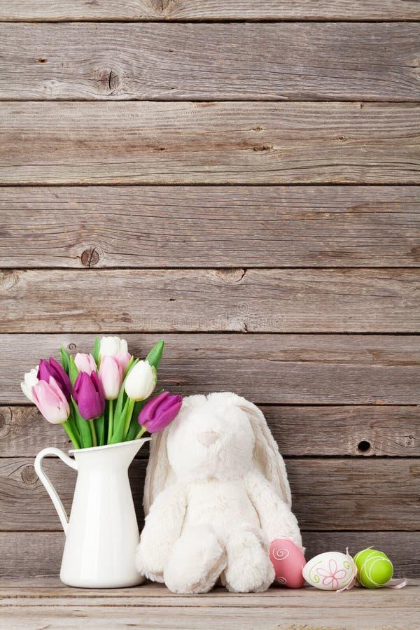 兔子玩具、复活节彩蛋和五颜六色的郁金香 库存图片