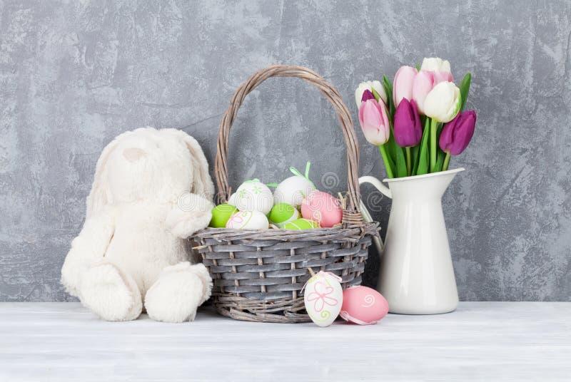 兔子玩具、复活节彩蛋和五颜六色的郁金香 免版税库存照片
