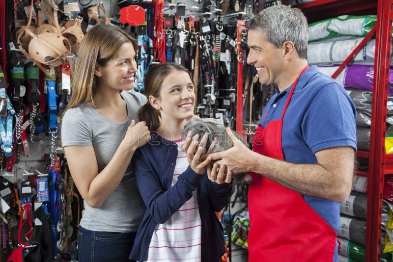 给兔子的推销员有母亲的女孩在宠物商店 图库摄影