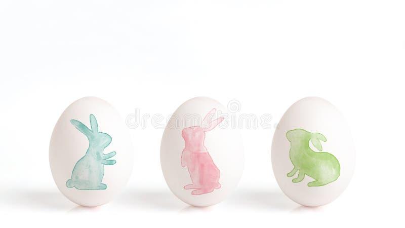 兔子绘与在一个白鸡蛋的水彩,在白色背景的复活节彩蛋,与逗人喜爱的兔宝宝的复活节设计 免版税库存图片