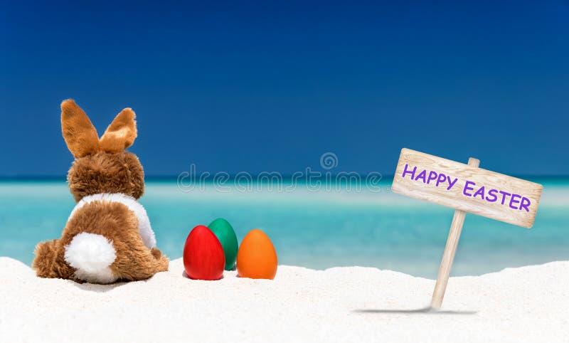 兔宝宝、复活节彩蛋和复活节快乐在海滩签字 免版税库存图片