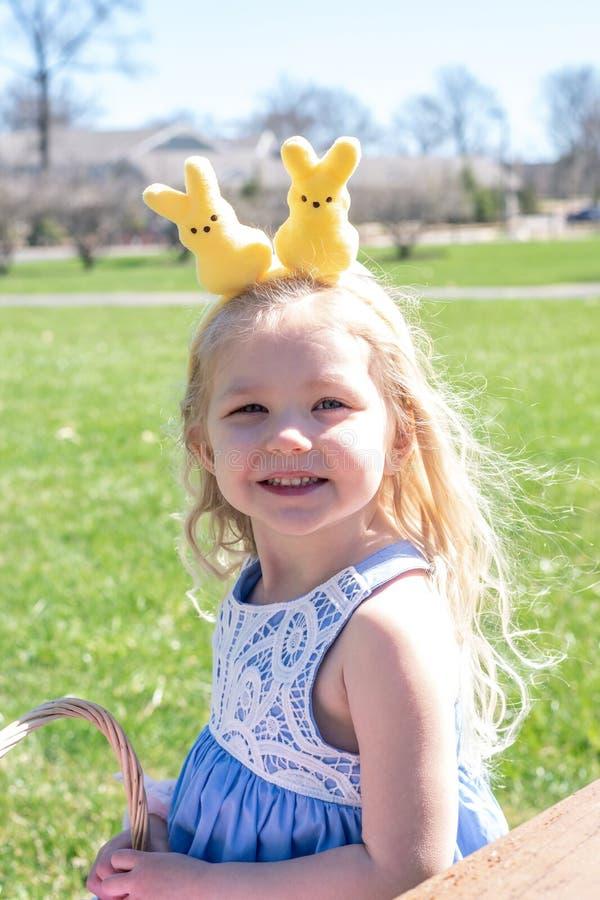 兔宝宝头饰带的逗人喜爱的女孩在复活节 库存照片