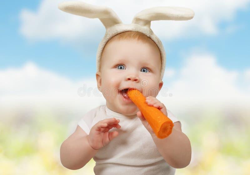 兔宝宝帽子的逗人喜爱的矮小的婴孩用红萝卜 库存照片