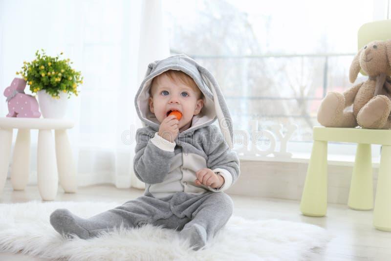 兔宝宝服装的逗人喜爱的矮小的婴孩坐地板 免版税库存图片