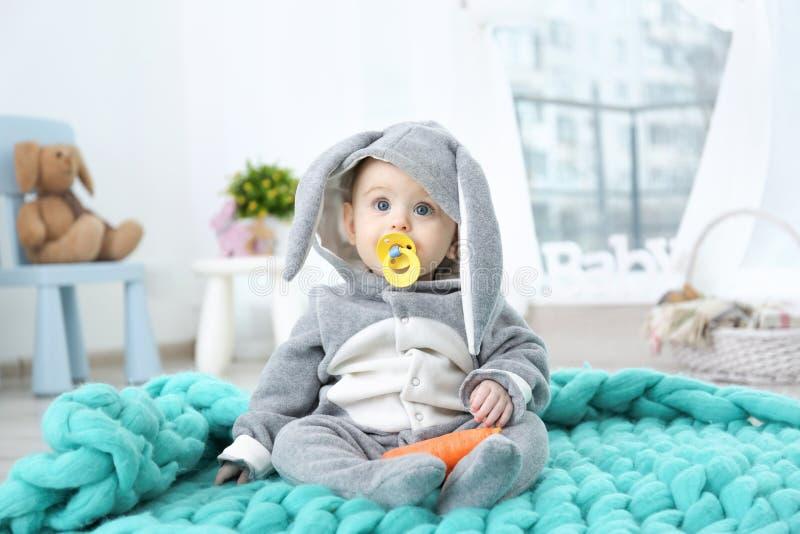 兔宝宝服装的逗人喜爱的矮小的婴孩坐格子花呢披肩 图库摄影