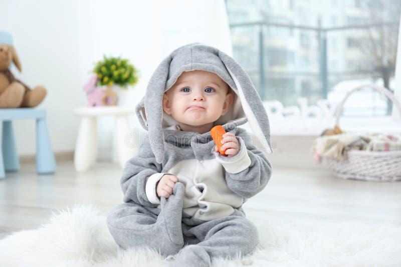 兔宝宝服装的逗人喜爱的矮小的婴孩坐毛茸的地毯 库存照片