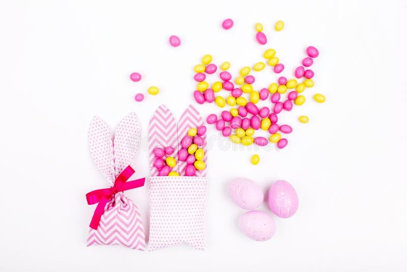 兔宝宝款待袋子用桃红色糖果和鸡蛋在白色背景; 库存照片