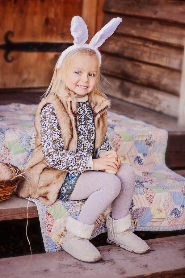 兔宝宝耳朵的愉快的儿童女孩复活节的坐乡间别墅梯子 免版税库存图片