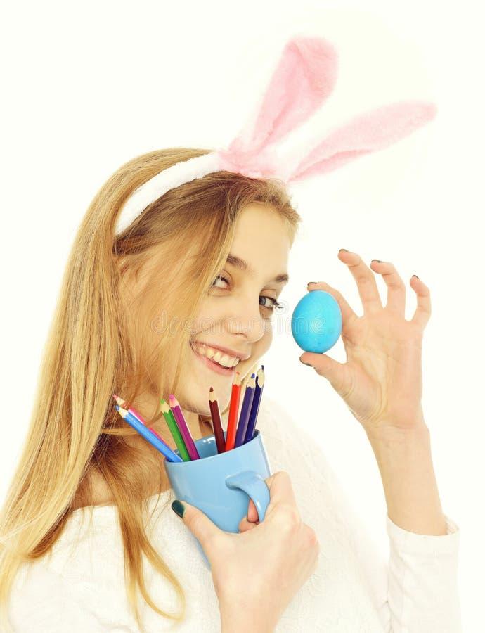 兔宝宝耳朵的愉快的复活节女孩用蓝色鸡蛋,铅笔 免版税库存照片