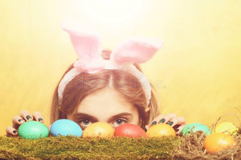 兔宝宝耳朵的愉快的复活节暗藏的女孩用五颜六色的鸡蛋 库存图片