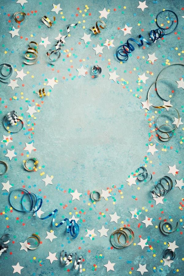 党、狂欢节或生日框架与五颜六色的五彩纸屑和飘带在葡萄酒蓝色台式视图 平的位置样式 节假日 免版税库存照片