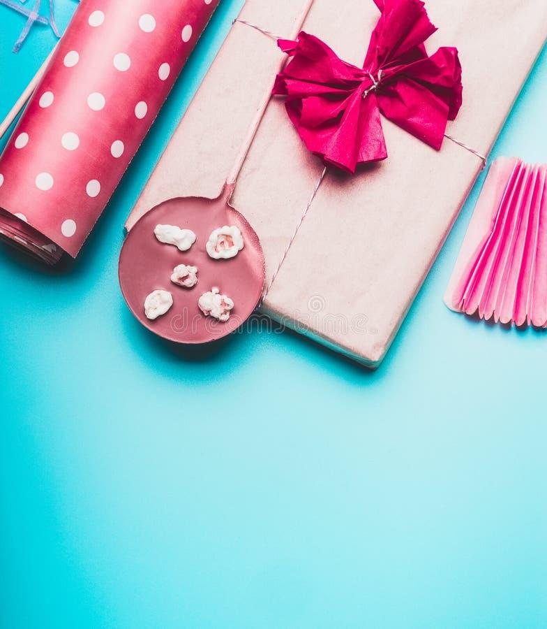 党与礼物盒、包装纸、装饰和巧克力蛋糕流行音乐的问候集合边界在蓝色背景,顶视图 图库摄影
