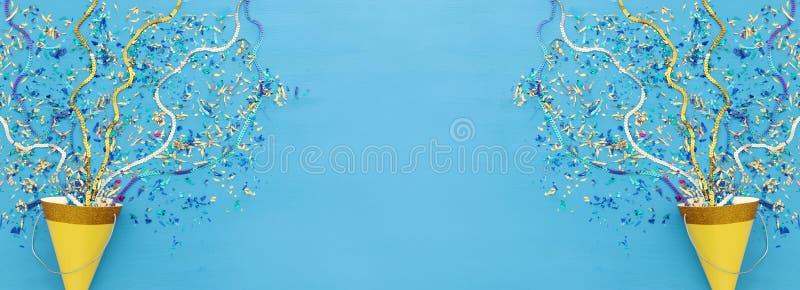 党五颜六色的五彩纸屑和小丑帽子在蓝色木背景 顶视图,平的位置 免版税库存照片