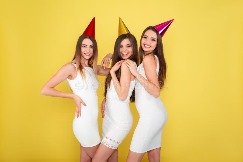 党和假日概念 豪华闪烁衣服饰物之小金属片的三名魅力妇女穿戴跳舞和有乐趣佩带的假日 免版税图库摄影