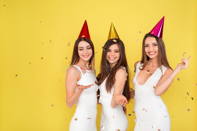 党和假日概念 豪华闪烁衣服饰物之小金属片的三名魅力妇女穿戴跳舞和获得与五彩纸屑的乐趣和 图库摄影