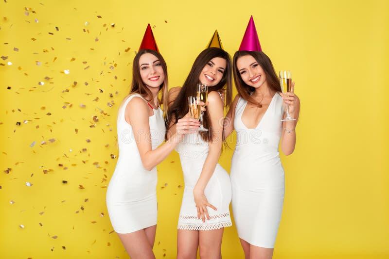 党和假日概念 豪华闪烁衣服饰物之小金属片的三名魅力妇女穿戴跳舞和获得与五彩纸屑的乐趣 库存照片