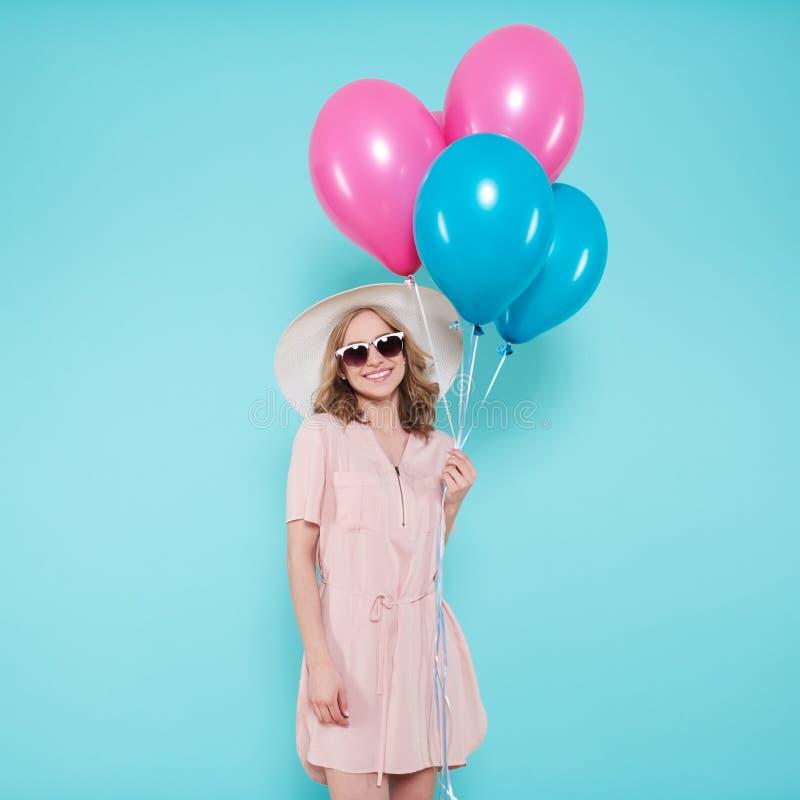 党拿着束五颜六色的气球的夏天礼服和草帽的华美的少妇,被隔绝在淡色蓝色 库存图片