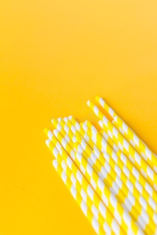 党的吸管在黄色背景 镶边党鸡尾酒秸杆 五颜六色的纸一次性环境友好 库存图片