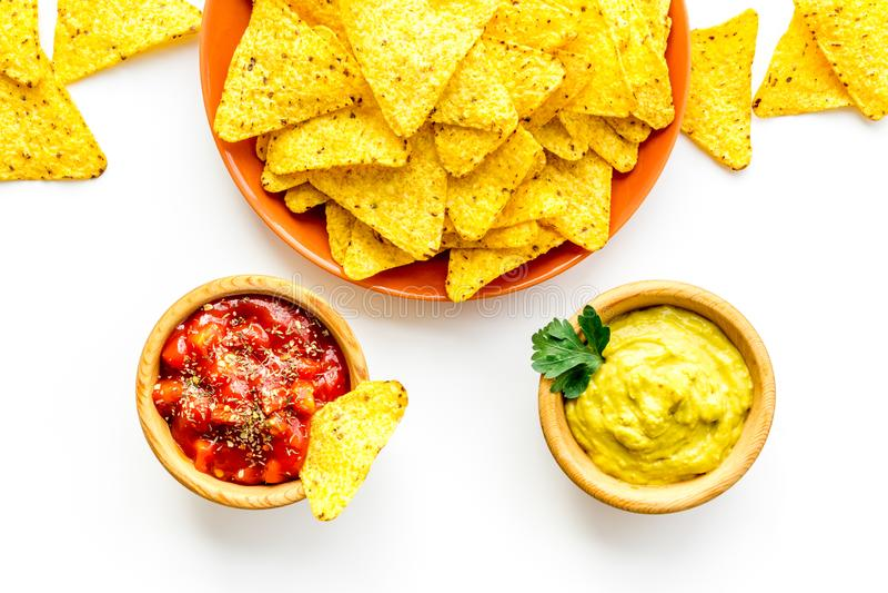 党的快餐 在辣调味汁和鳄梨调味酱捣碎的鳄梨酱sause附近的墨西哥烤干酪辣味玉米片在白色背景顶视图 库存图片