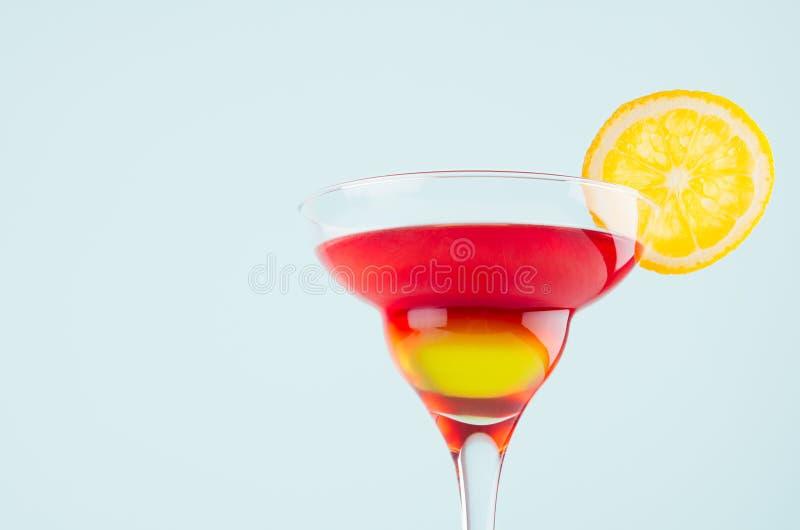 党的明亮的夏天饮料玛格丽塔酒与红色和黄色酒,在薄荷的颜色背景,特写镜头,细节的橙色切片 免版税图库摄影